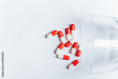 red and white capsules near overturned glass on white background, suicide prevention concept