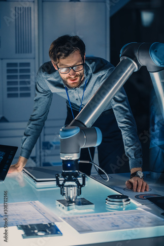 Photo Vertical Shot of a Mechanical Engineer Works with Futuristic Robotic Arm and Programms it For Moving Metal Object