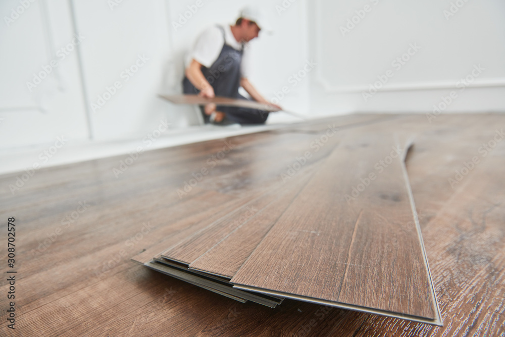 Fototapeta worker laying vinyl floor covering at home renovation
