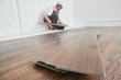 Leinwanddruck Bild - worker laying vinyl floor covering at home renovation