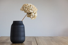 A Black Ceramic Vase With A Dr...