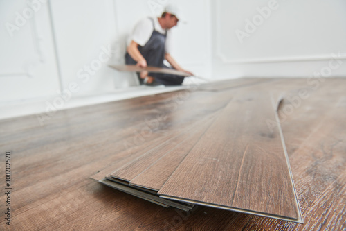 Obraz na płótnie worker laying vinyl floor covering at home renovation