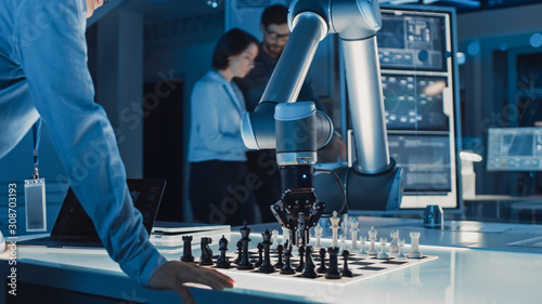 Obraz na plátně Professional Japanese Development Engineer is Testing an Artificial Intelligence Interface by Playing Chess with a Futuristic Robotic Arm