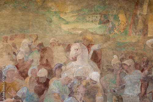 Pisa, Tuscany / Italy - 08/20/2019: Medieval mural in Camposanto cemetery of the Campo dei Miracoli. Fresco in Monumental Cemetery. Camposanto Monumentale painting Group of people and horse rider.