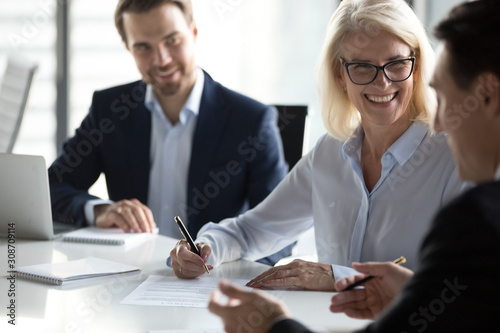 Fotomural Smiling mature businesswoman signing contract, agreement at meeting