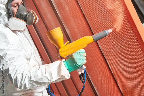 Fotografía polymer coating of metal detail with powder spraying gun