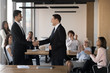 Executive manager shaking hand of Arabian employee at company meeting