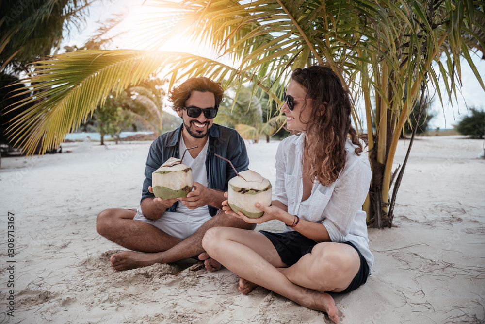 Fototapeta A beautiful young couple joyfully sits on white sand under a palm tree with coconuts in their hands on the seashore under a green palm tree. Honeymoon Travel and Vacation on the Tropical Ocean.