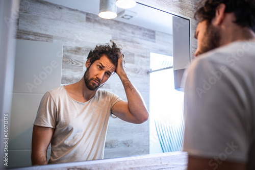Fotografia, Obraz Handsome young man touching his hair with hand and grooming in bathroom at home