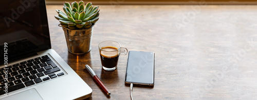 Fototapeta Workplace. Computer laptop and mobile phone on a wood office desk, banner, copy space obraz