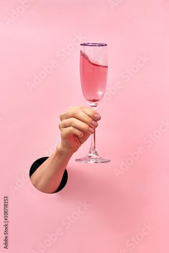Kieliszek do wina różanego w kobiecej dłoni z dziury w ścianie.