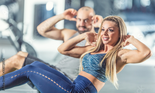 Valokuva  Woman and man athletic couple strengthen abdominal muscles in gym