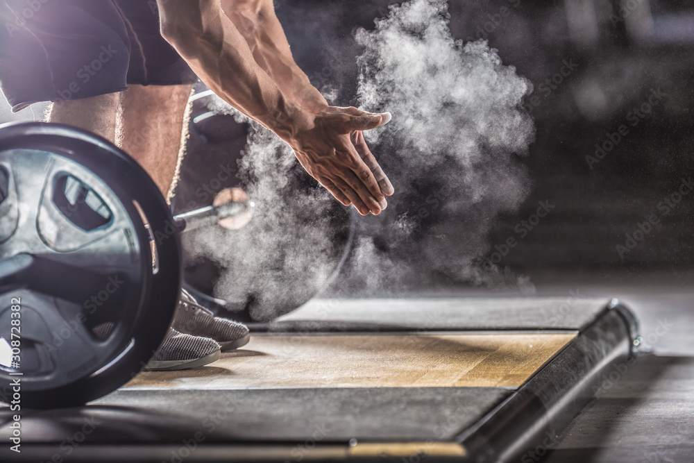 Fototapeta Muscular weightlifter clapping hands before barbell workout at the gym with dumbbells
