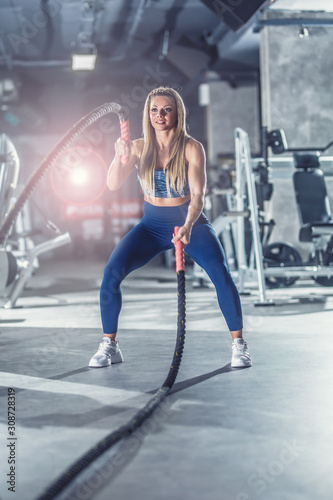 Cuadros en Lienzo Sporty woman exercising with battle ropes at the fitness gym