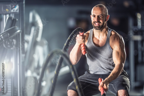 Fotomural Muscular man exercising with battle ropes at the fitness gym