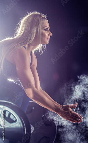 Fotografía Muscular weightlifter woman clapping hands before barbell workout at the gym wit