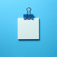 Blue Memo Pad Sticky Note And Clip On Blue Background