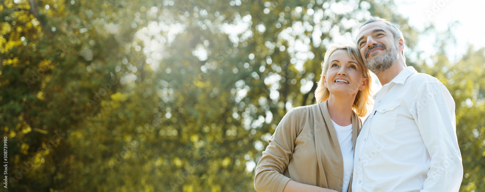 Fototapeta Senior Caucasian couple hugging in park. Family with a happy smile feels relaxed with nature in the morning. Or in the evening. Enter  elderly society And retire from work. Concept health insurance