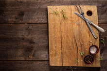 Chopping Board On Dark, Wooden Table. Rosemary, Pepper, Salt. Copy Space.