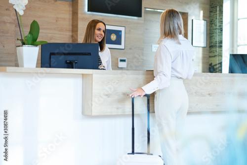 Slika na platnu Receptionist and businesswoman at hotel front desk