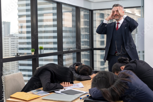 Obraz na plátně Moody or stress boss with lazy or tired teamwork sleep on meeting table in offic