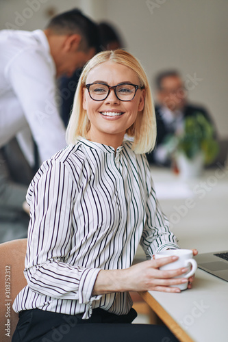Smiling young businesswoman drinking a coffee in an office