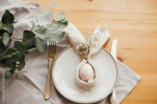 Fotografie, Obraz Stylish Easter brunch table setting with egg in easter bunny napkin on  table