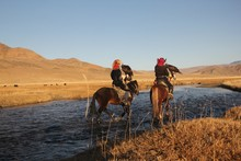 Picture Of Two Horseriders In A River Surrounded By A Deserted Valley With Hills On The Background
