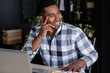 Positive young successful african american designer working on a new project while sitting at a table with a laptop. Handsome smiling mixed race businessman rejoices in career growth