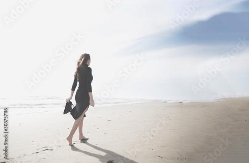 mujer caminando por la playa Canvas-taulu