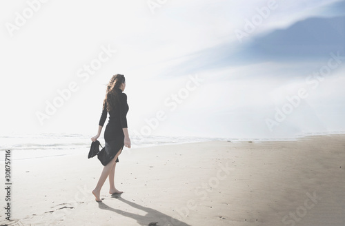 Fototapeta mujer caminando por la playa