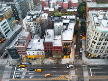 Overhead View Of New York City Street Scene With Taxis Driving Down Bowery Past The Buildings Of The Nolita Neighborhood In Manhattan