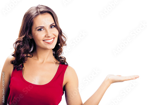 Fototapeta Happy smiling lovely girl, showing something or product or copy space for some text or slogan, isolated over white background. Brunette model in casual red clothing at studio picture obraz