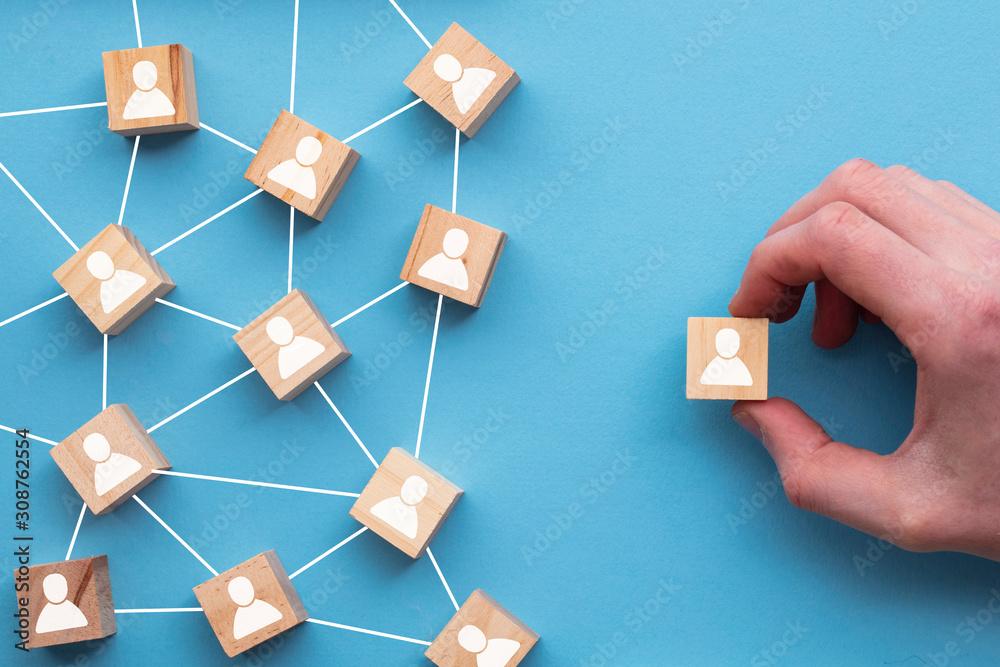 Fototapeta Hand choosing a wooden block from a set. Business choice concept