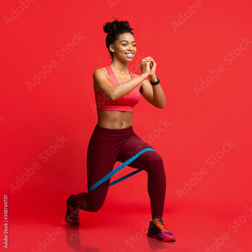 obraz PCV Cheerful afro fitness girl making working out with resistance band