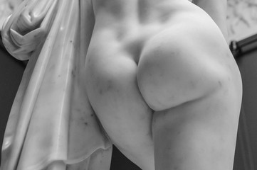 Antique marble woman ass sculpture. Detail of the butt of the statue of marble with solid buttocks