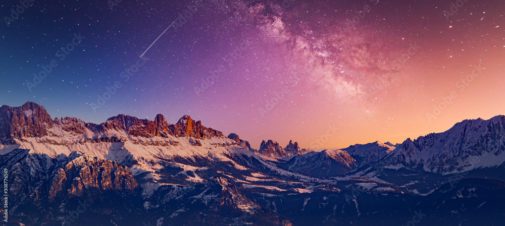 Fototapeta Snowy rocky mountain with a beautiful starry night, space fort text
