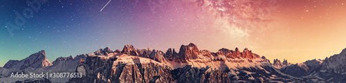 Fototapeta Snowy rocky mountain with a beautiful starry night, space fort text obraz