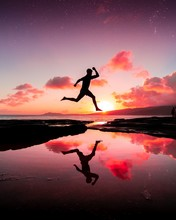 Vertical Shot Of A Person Jumping Over The Water And His Reflection In It Under The Pink Sunset Sky