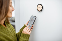 Woman Dressed In Green Sweater Regulating Heating Temperature With A Modern Wireless Thermostat And Smart Phone At Home. Synchronization Of Thermostat With Mobile Devices Concept