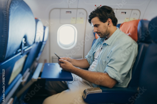The guy is flying in an airplane, listening to music.