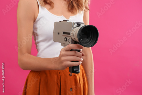 Obraz na plátne Woman with vintage video camera on crimson background, closeup