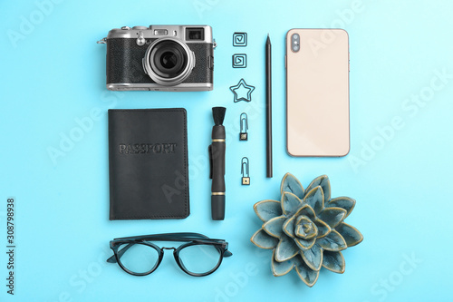 Obraz Flat lay composition with camera for professional photographer and smartphone on light blue background - fototapety do salonu