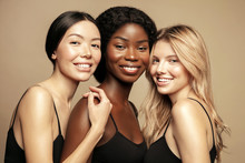 Beauty. Multi Ethnic Group Of Womans With Diffrent Types Of Skin  Together And Looking On Camera. Diverse Ethnicity Women - Caucasian, African And Asian Posing And Smiling Against Beige Background.