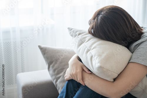 Woman sitting on couch and hugging a pillow, loneliness and sadness concept