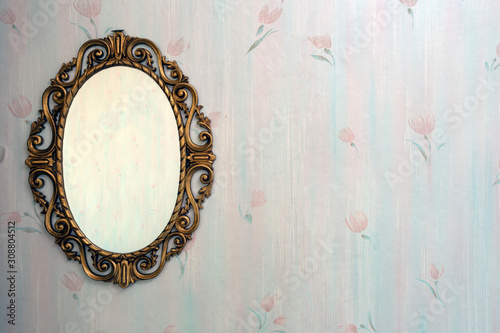 Obraz Old antique gold mirror hanging in a vintage room with old pattern wallpaper - fototapety do salonu