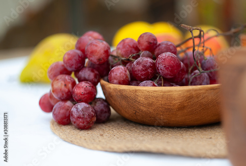 Photo close-up of red grape in rustic ceramic plate on a white tablecloth with blurred
