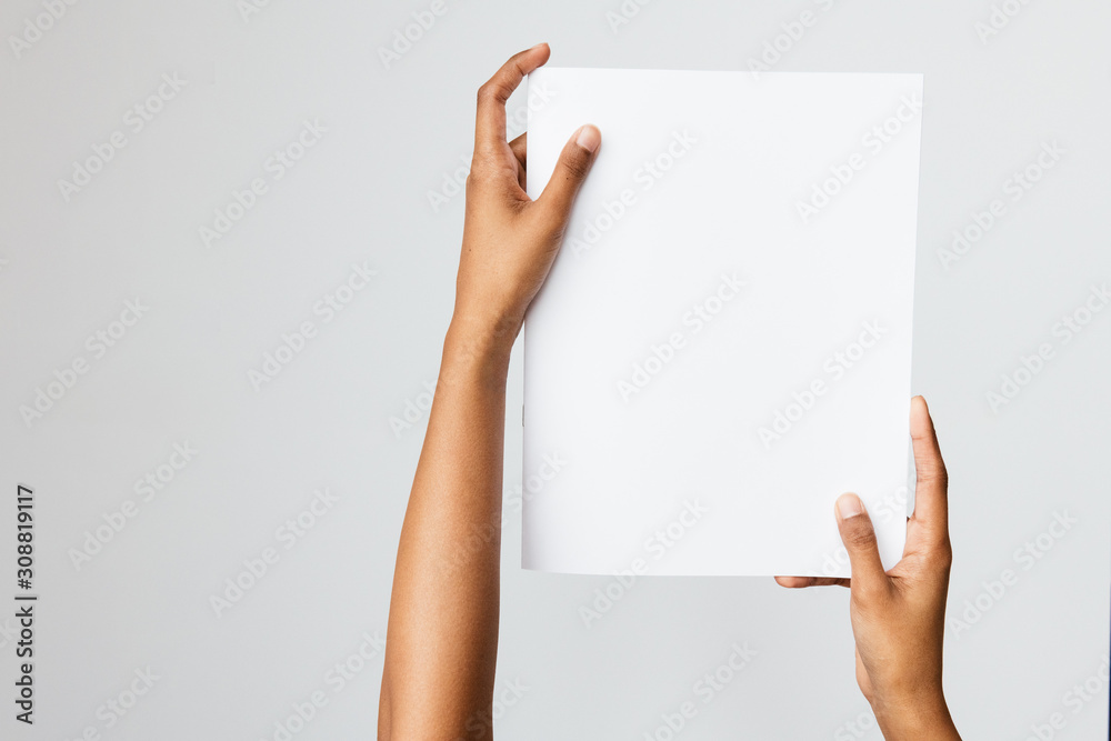 Fototapeta Woman of color holding a letter size or A4 brochure mockup