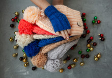 Hands Of Young Beautiful Woman In Blue Mittens Holding Many Colored Bright Warm Winter Hats. On A Gray Background Are Bright Christmas Decorations.