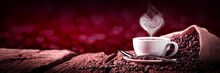 Coffee With Heart Shaped Steam On Old Weathered Table And Red Heart Bokeh Background - Valentine's Day Concept